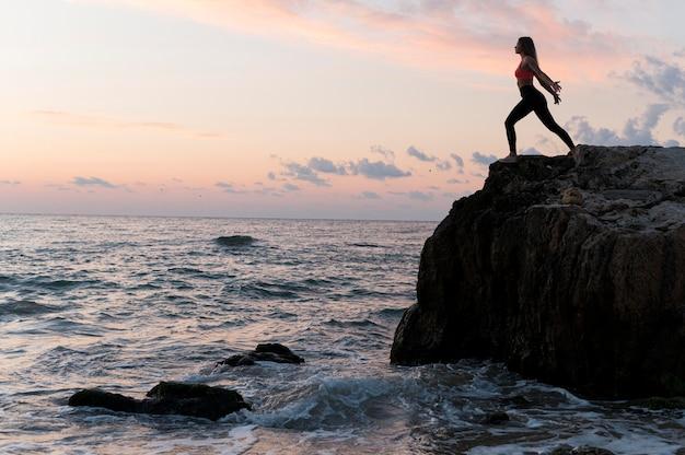 Mulher em roupas esportivas em uma costa com espaço de cópia