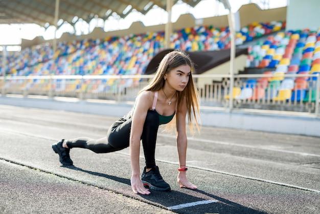 Mulher em roupas esportivas fazendo corrida matinal no estádio