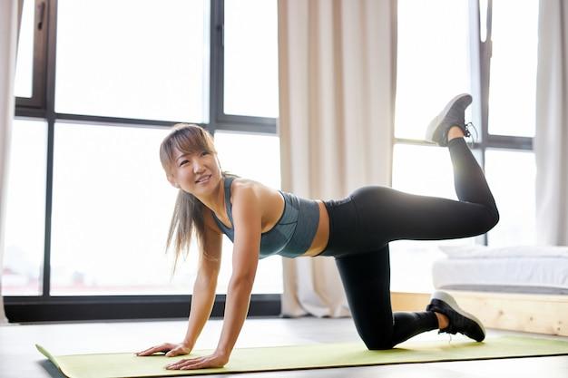 Mulher em roupas esportivas, fazendo exercícios de alongamento em casa, na sala iluminada. esporte, estilo de vida saudável e conceito de recreação.