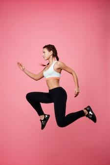 Mulher em roupas esportivas finge correr no ar, pulando alto