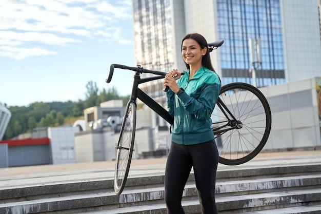 Mulher em roupas esportivas indo para um passeio de bicicleta