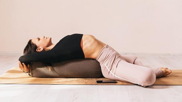 Mulher em roupas esportivas praticando ioga fazendo exercícios supta baddha konasana com almofada sob as costas em um tapete no estúdio
