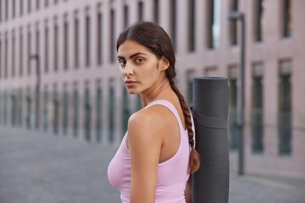 Mulher em roupas esportivas retorna após treino no clube usa roupas esportivas passeios na cidade passa por alguns edifícios participa de treinamento de aula de clube de ioga