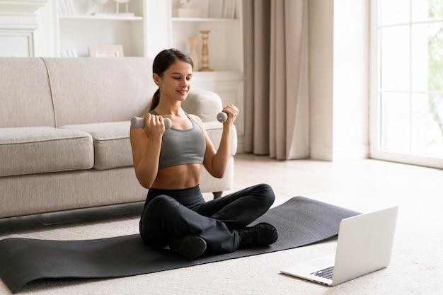 Mulher em roupas esportivas se exercitando em casa