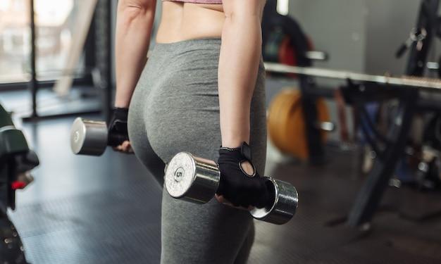 Mulher em roupas esportivas segurando halteres nas mãos na academia