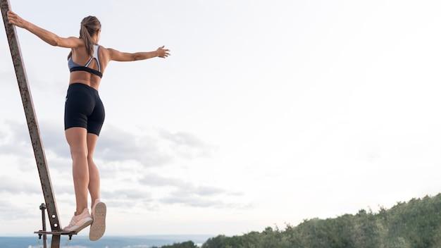 Mulher em roupas esportivas segurando-se em uma barra de metal com espaço de cópia
