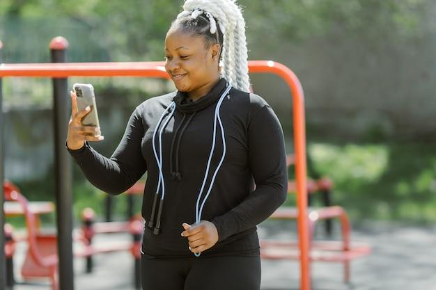 Mulher em roupas esportivas segurando um smartphone
