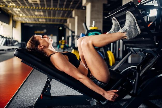 Mulher em roupas esportivas treina na máquina de exercícios