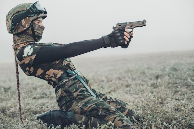 Mulher em roupas militares com uma arma nas mãos dela