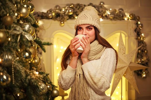 Mulher em roupas quentes, bebendo café em casa na decoração de ano novo