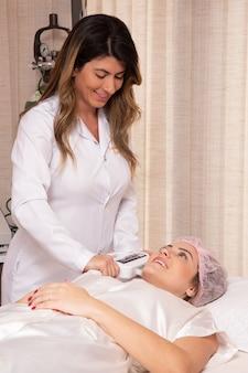 Mulher em salão de beleza profissional durante procedimento de fotoepilação