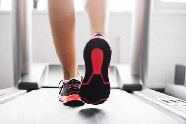 Mulher em sapatos esportivos correndo em esteira