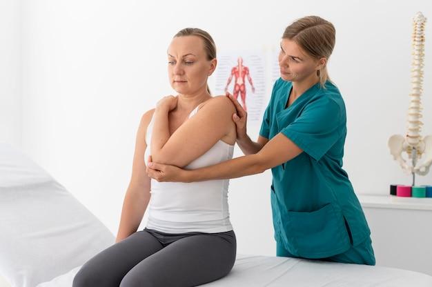 Mulher em sessão de fisioterapia em clínica