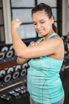 Mulher, em, sportswear, mostrando, dela, músculos, em, a, ginásio
