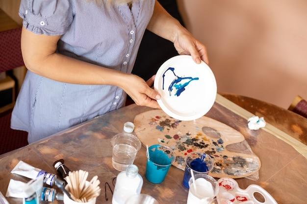 Mulher em sua oficina no trabalho. ela escolhe tons de azul e turquesa para seu trabalho. inspiração e criatividade. pintura de interiores. design moderno. estilo de vida. hobbies e artesanato.