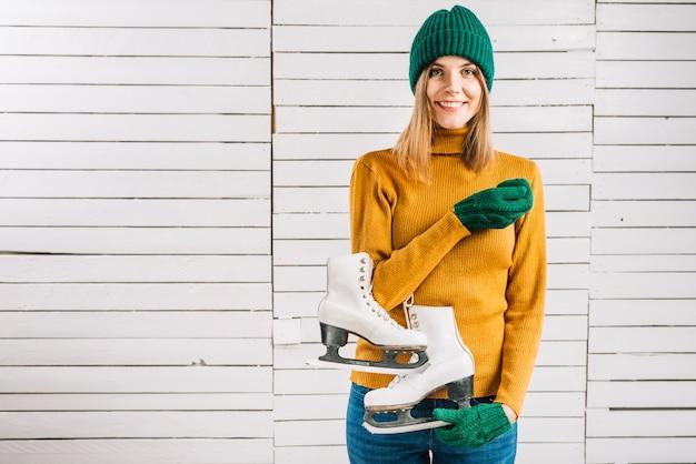 Mulher, em, suéter amarelo, segurando, patins