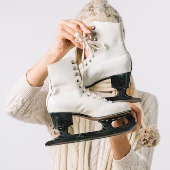 Mulher, em, suéter, segurando, branca, patins