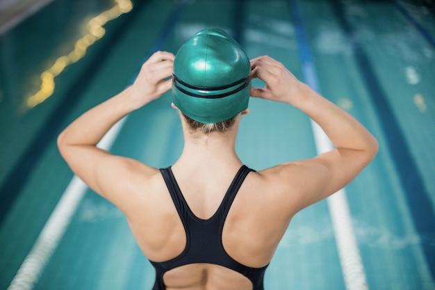 Mulher, em, swimsuit, ajustar, dela, óculos proteção, em, a, piscina