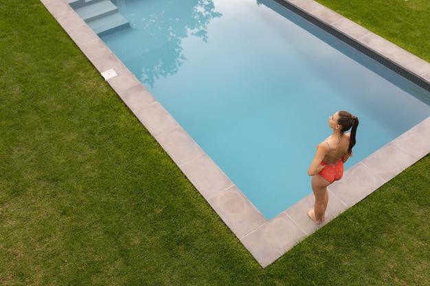 Mulher, em, swimwear, ficar, com, mãos quadril, perto, poolside, em, a, quintal