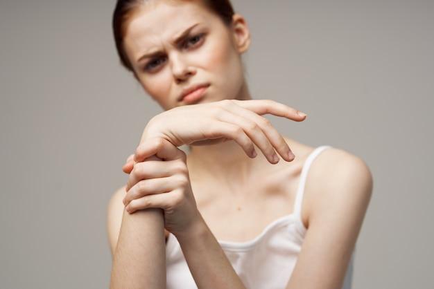 Mulher em t-shirt branca braço dor artrite doença crônica de fundo claro. foto de alta qualidade