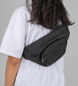 Mulher em t-shirt branca carrega a bolsa casual no ombro com um gesto ativo e fácil.