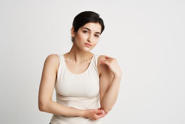 Mulher em t-shirt branca creme corporal rejuvenescimento da saúde. foto de alta qualidade
