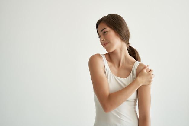 Mulher em t-shirt branca dor nas articulações problemas de saúde reumatismo. foto de alta qualidade