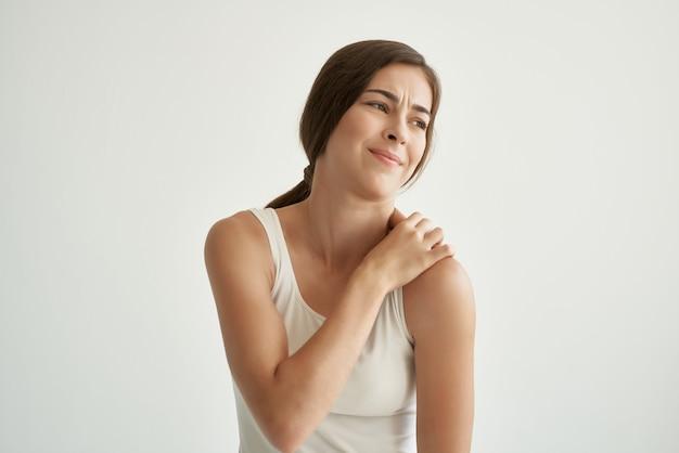 Mulher em t-shirt branca problemas de dor nas articulações com reumatismo. foto de alta qualidade
