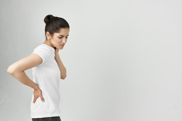 Mulher em t-shirt branca problemas de saúde dor nas costas. foto de alta qualidade