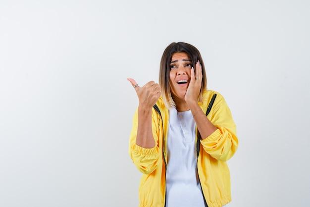 Mulher em t-shirt, jaqueta aparecendo o polegar, mantendo a mão na bochecha e olhando animada, vista frontal.
