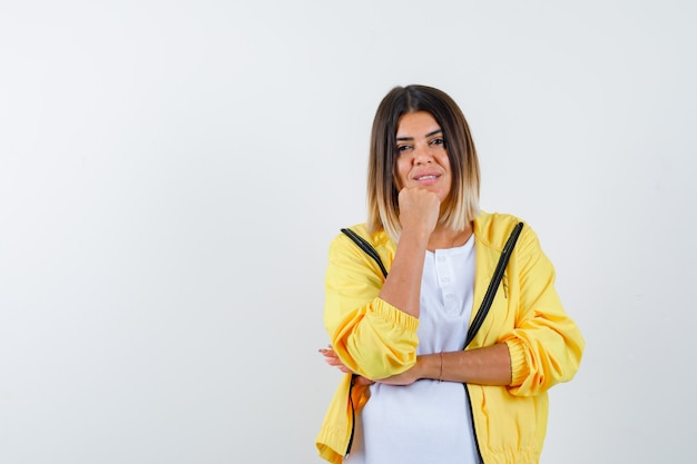 Mulher em t-shirt, jaqueta, apoiando o queixo no punho e olhando otimista, vista frontal.