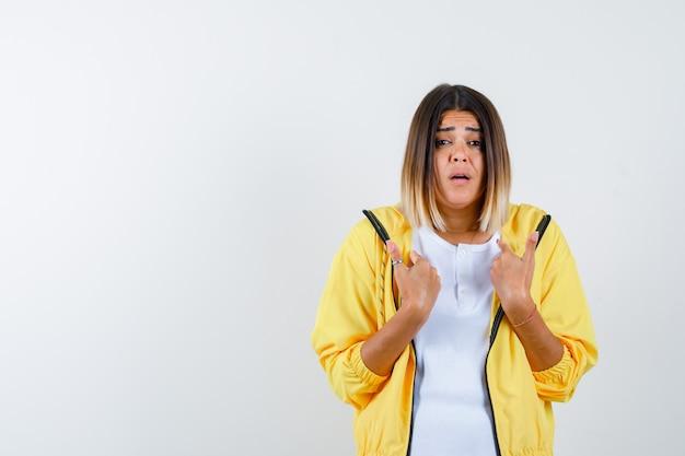 Mulher em t-shirt, jaqueta apontando para si mesma e parecendo confusa, vista frontal.