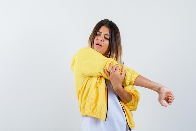 Mulher em t-shirt, jaqueta esticando os braços e parecendo relaxada, vista frontal.