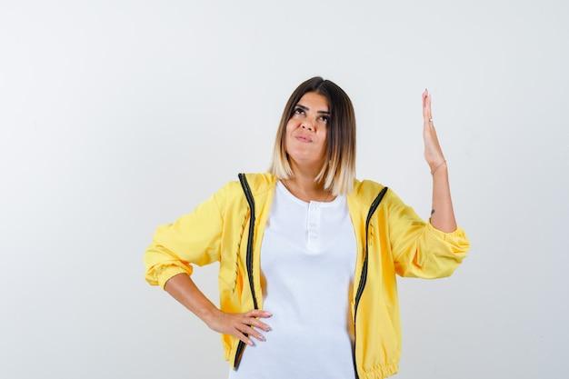 Mulher em t-shirt, jaqueta levantando a mão enquanto olha para cima e parece um sonho, vista frontal.