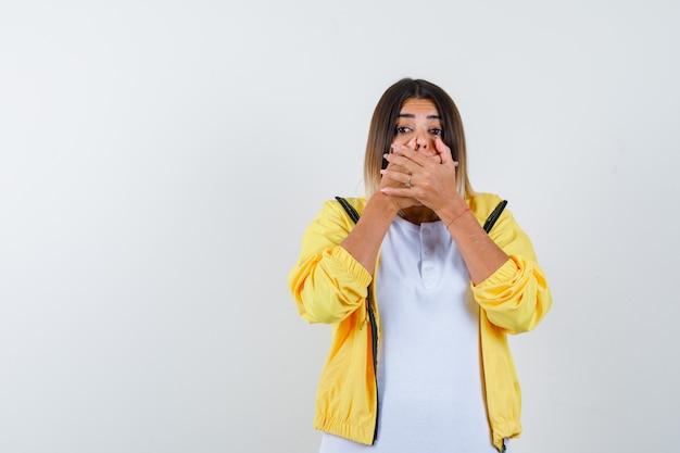 Mulher em t-shirt, jaqueta, mantendo as mãos na boca e parecendo assustada, vista frontal.
