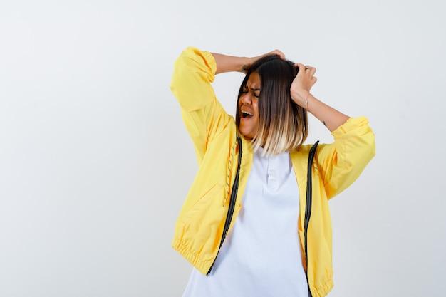 Mulher em t-shirt, jaqueta, mantendo as mãos na cabeça enquanto grita e parece deprimida, vista frontal.