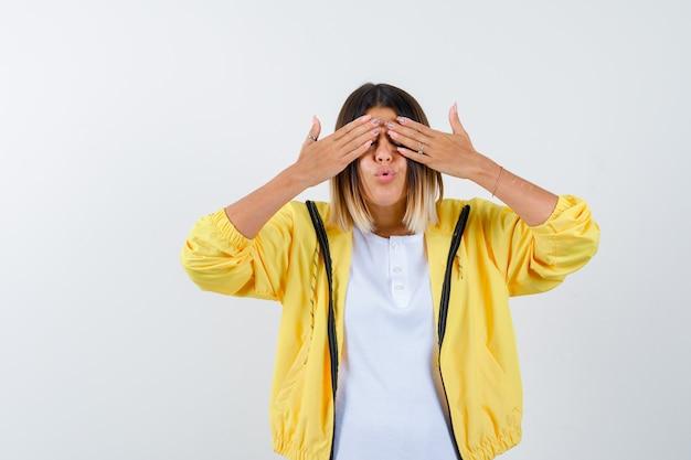 Mulher em t-shirt, jaqueta, mantendo as mãos nos olhos, fazendo beicinho nos lábios e parecendo animada, vista frontal.