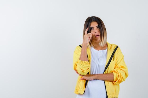 Mulher em t-shirt, jaqueta, mantendo o dedo nas têmporas e olhando pensativa, vista frontal.