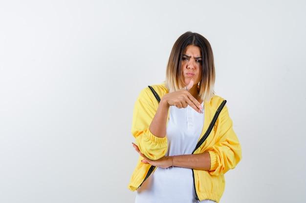 Mulher em t-shirt, jaqueta mostrando gesto de arma e parecendo confiante, vista frontal.