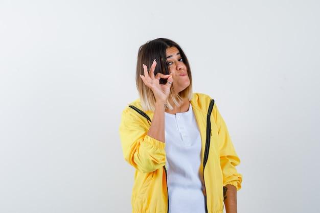 Mulher em t-shirt, jaqueta mostrando gesto ok e parecendo confiante, vista frontal.