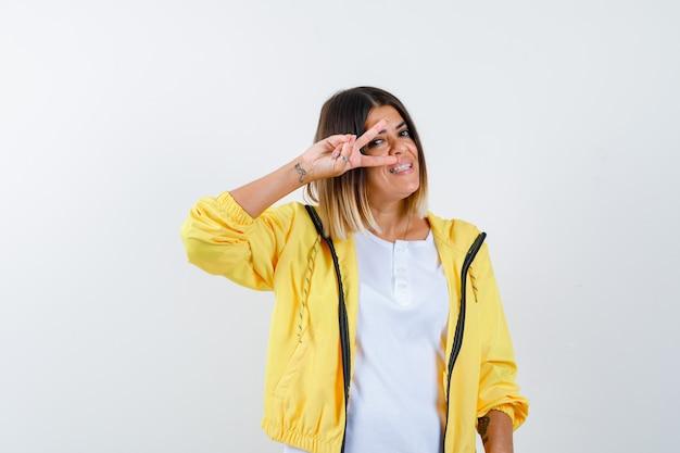 Mulher em t-shirt, jaqueta mostrando o sinal de v perto do olho e olhando alegre, vista frontal.