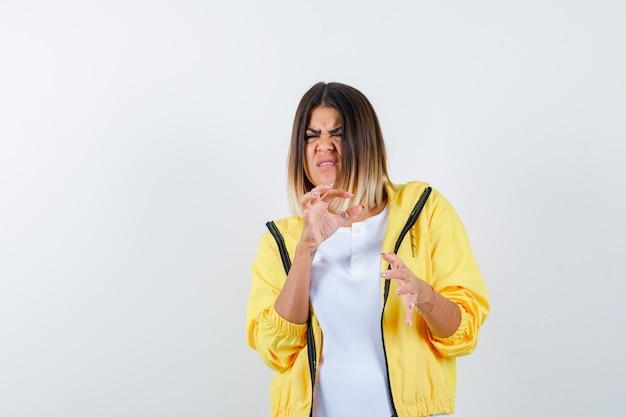 Mulher em t-shirt, jaqueta mostrando sinal de tamanho pequeno e parecendo desapontada, vista frontal.