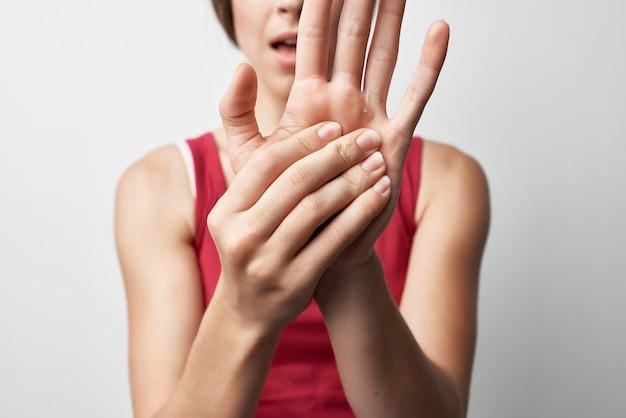 Mulher em t-shirt vermelha tratamento de mão lesão dor nas articulações. foto de alta qualidade