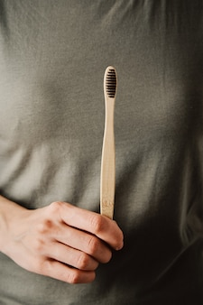 Mulher em t-short verde segura a escova de dentes de bambu. itens ecológicos e conceito de desperdício zero