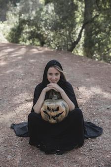 Mulher, em, terno bruxa, sentando, ligado, solo, e, segurando, abóbora