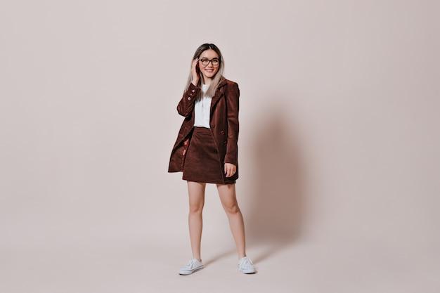 Mulher em terno de veludo cotelê e óculos posando na parede bege