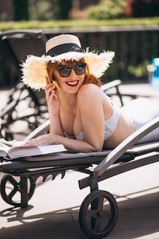 Mulher, em, terno natação, mentindo, ligado, um, cama, e, lendo um livro