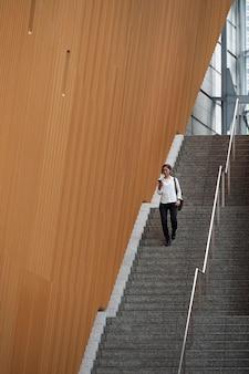 Mulher em tiro certeiro descendo escadas