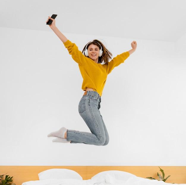 Mulher em tiro completo pulando na cama