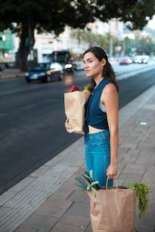 Mulher em tiro médio carregando sacolas de papel
